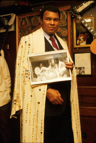 Mohammod Ali wearing and holding picture of robe Elvis gave him