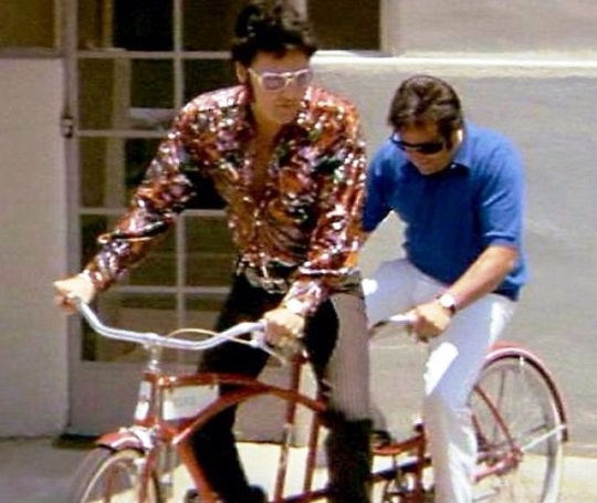 Elvis and Joe Esposito riding a bike
