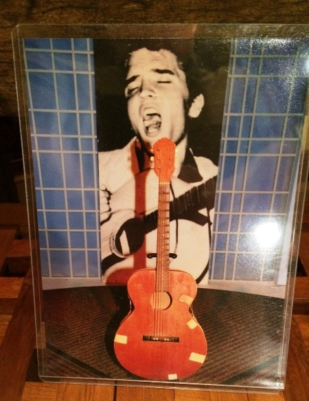 Elvis Presley's First Guitar in front of Picture