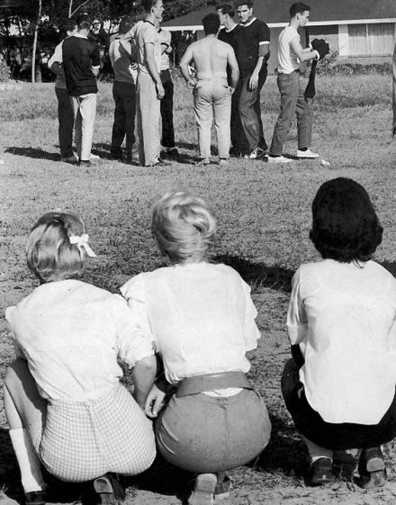 Elvis and his friends playing a game of football with some very interested girls watching on