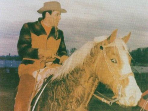 Elvis riding in front of lake