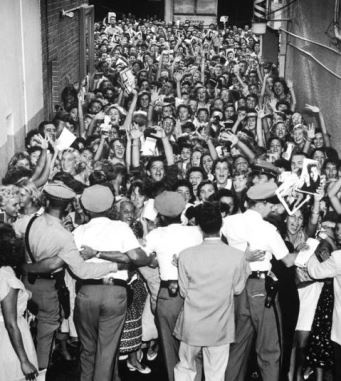 A screaming crowd of teenage girls are restrained by police outside an Elvis concert in 1956.